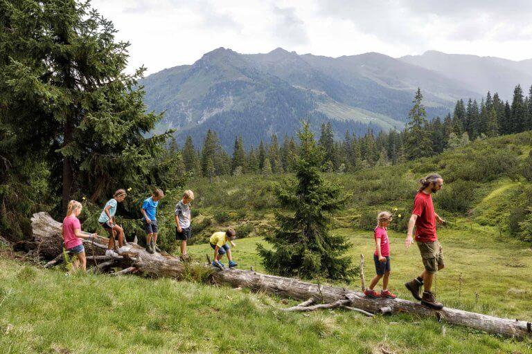 Familie läuft über Baumstamm