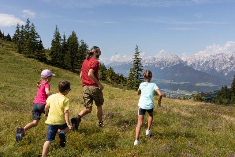 Familie läuft auf Bergwiese