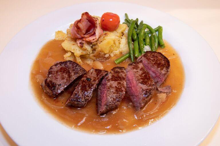Rinderrückensteak mit Zwiebelsauce, grünen Bohnen und Bratkartoffeln